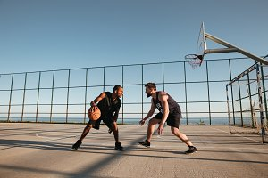 Portrait of two young men playing basketball at the playground