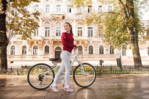 Beautiful woman walking with her bicycle in the city
