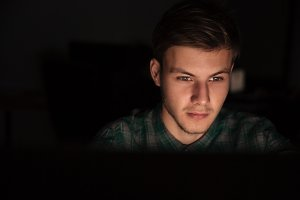 Attractive young man using computer in dark room