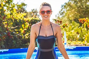happy active woman in swimming pool in sunglasses