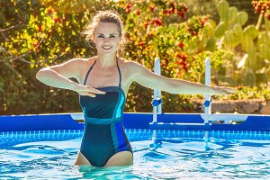 active woman in swimming pool doing water aerobics