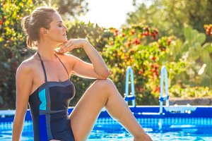 relaxed healthy woman sitting on swimming pool and relaxing