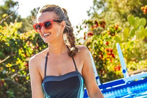 woman in swimming pool looking into distance in sunglasses