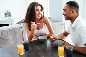 Cheerful young couple smiling and having breakfast on the kitchen