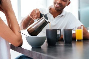Man pouring coffee into cups and having breakfast with girlfriend