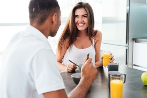 Cheerful young couple talking and having breakfast together
