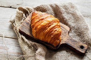 Fresh croissant on wooden board