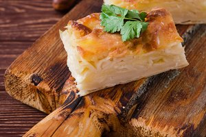 Traditional Georgian cheese layer pie Achma on wooden background. Selective focus