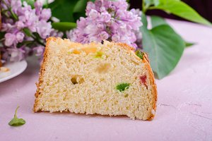 Slice of pannetone cake with cugar fruits and lilac flowers on spring background. Selective focus