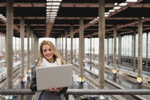 Woman holding laptop at the station smile