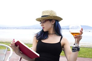 Young woman in straw hat reading book and drinking beer in a bar