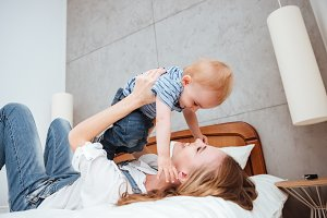 Mother playing and having fun with little son on bed