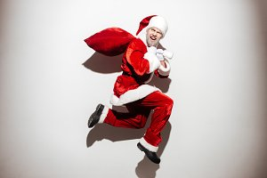 Cheerful bad man santa claus holding gift sack and running
