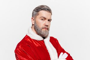 Man in santa claus costume standing with arms crossed