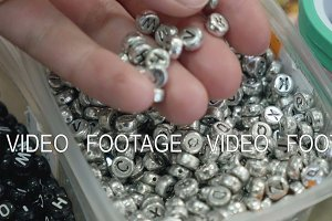 Young girl look at alphabetic accessories for jewelry