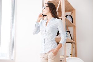 Cheerful businesswoman in her office talking by phone