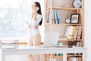Businesswoman standing near window and talking by phone