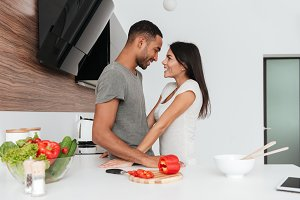Happy loving couple in the kitchen hugging while cooking.