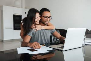 Happy loving couple using laptop and analyzing their finances