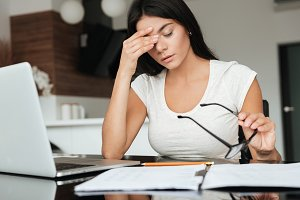 Tired woman analyzing home finances while suffering eyestrain