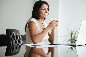 Happy woman analyzing home finances while drinking juice