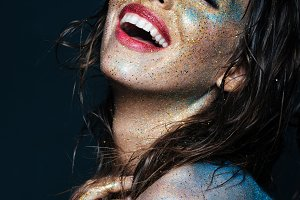 Beauty portrait of cheerful young woman with blue glitter makeup