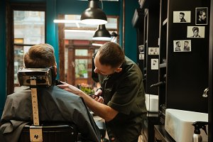 Handsome young man getting beard haircut while sitting in chair