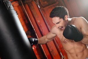 Screaming strong boxer training in a gym with punchbag