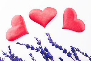 Three red hearts next to lavender flower on white background.