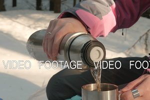 Young girl pours tea from a thermos into a mug