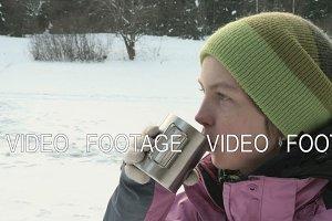 Girl drinks coffee on the street in winter