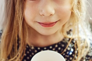 Little girl with milk cup