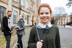 Redhead woman student with backpack standing outside at the campus