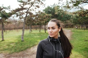 Female attractive runner in warm clothes and earphones