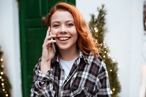 Laughing young woman with red hair talking by phone outdoors