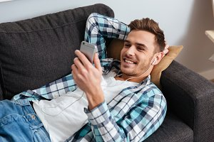 Happy man lies on sofa and chatting while listening music