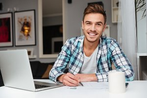 Joyful bristle man using laptop computer while writing notes