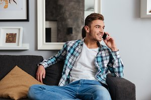 Young cheerful man on sofa talking by his phone