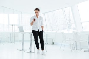 Young handsome man using mobile phone