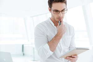 Concentrated man writing notes in notebook.