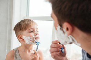 Father and son shaving in bathroom looking at each other
