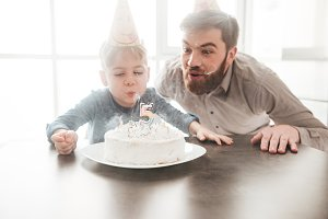 Cheerful father sitting near birtday cake with his little son.