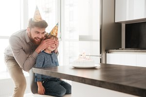 Happy young father with birthday son and covering his eyes.