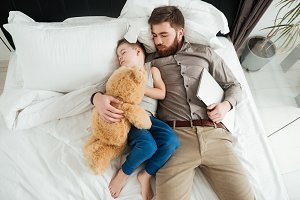 Boy sleeping in bed with his bearded father and toy.