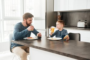Young father eating at kitchen with his little son