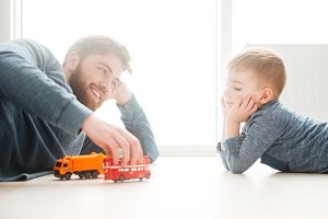 Boy playing on the floor with his bearded father.