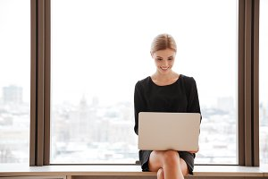 Young lady sitting in office near window while using laptop