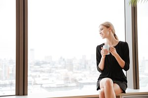 Young cheerful lady worker drinking hot tea near window.