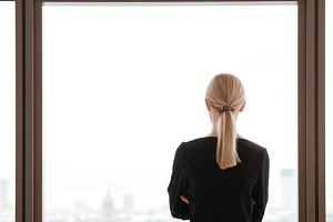 Back view image of young woman worker looking at window.