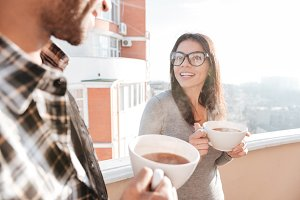 Young happy couple drinking coffee while standing on roof.